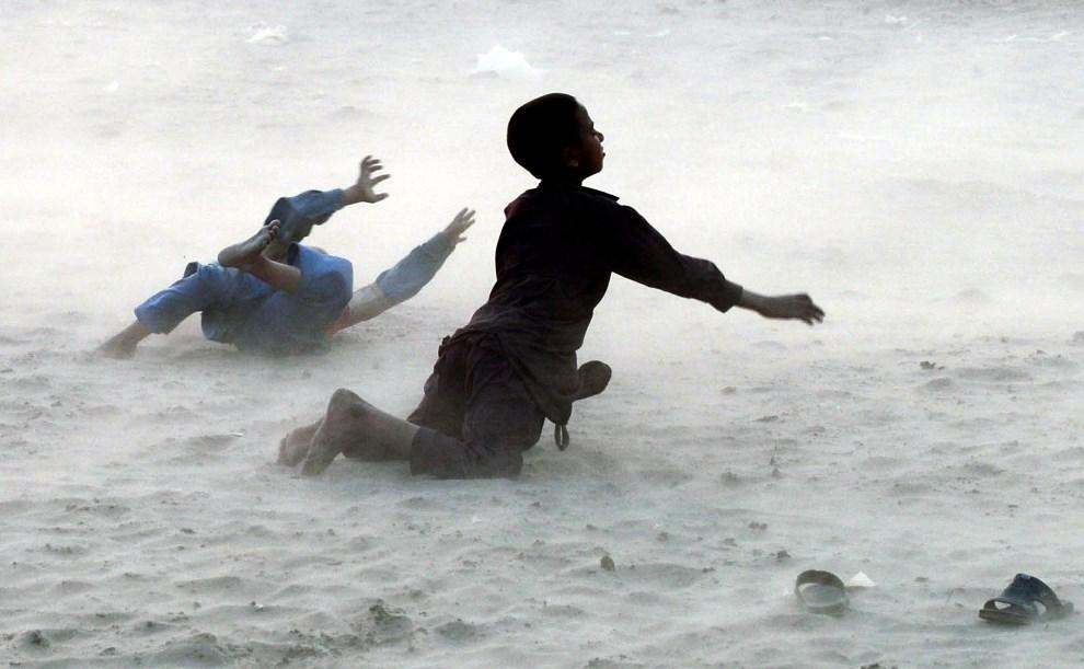 20.PAKISTAN, Lahore, 10 marca 2014: Chłopcy bawią się podczas burzy piaskowej. AFP PHOTO/Arif ALI