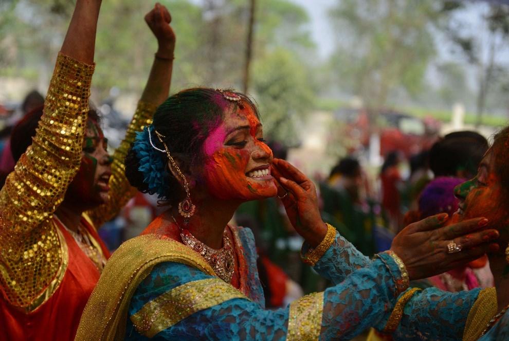 20.INDIE, Siliguri, 16 marca 2014: Kobiety malujące twarze kolorowymi proszkami. AFP PHOTO / Diptendu DUTTA