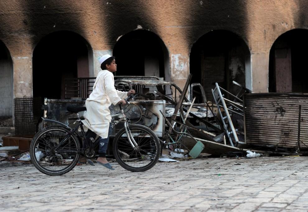 20.ALGIERIA, Ghardaia, 16 marca 2014: Chłopiec na rowerze w zniszczonej, podczas zamieszek, części miasta. AFP PHOTO / FAROUK BATICHE