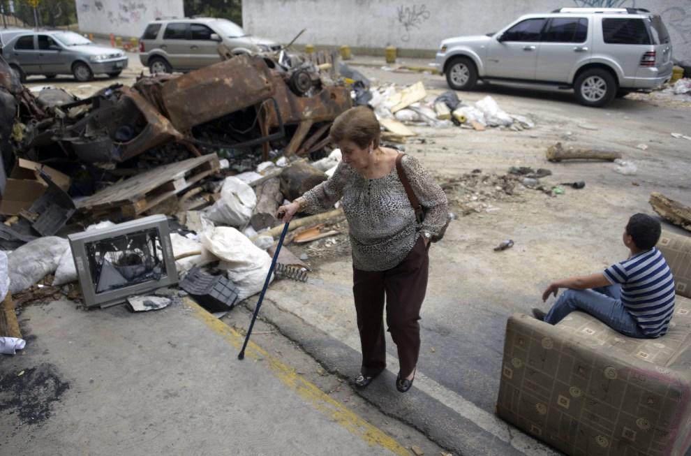 22.WENEZUELA, Caracas, 25 lutego 2014: Kobieta przechodzi obok barykady wniesionej w centrum Caracas. AFP PHOTO/ Raul Arboleda