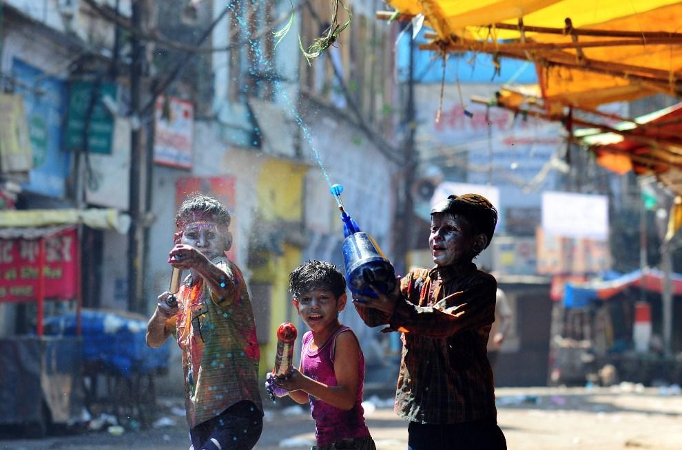 22.INDIE, Allahabad, 17 marca 2014: Dzieci pokryte kolorowymi farbami podczas zabawy z okazji Holi. AFP PHOTO/SANJAY KANOJIA