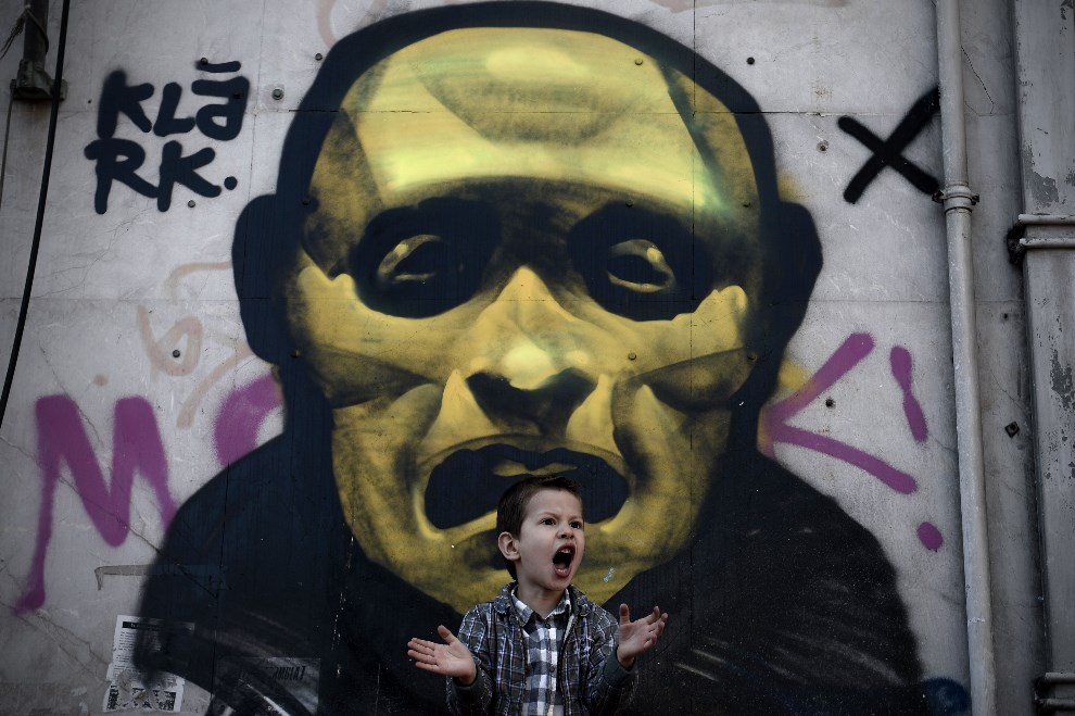 22.GRECJA, Ateny, 25 marca 2014: Chłopiec przyglądający się paradzie wojskowej w Dniu Niepodległości. AFP PHOTO / ARIS MESSINIS