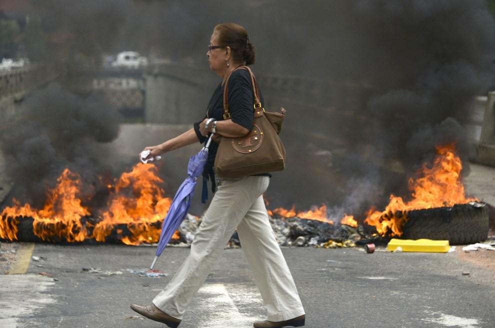 23.WENEZUELA, Caracas, 24 lutego 2014: Kobieta mija podpalone przez protestujących opony. AFP PHOTO/ Raul Arboleda