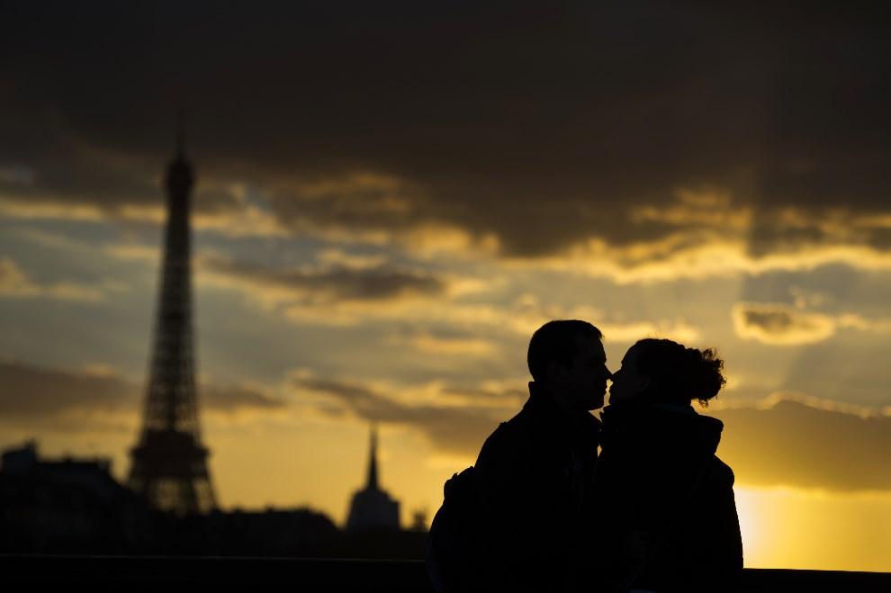 23.FRANCJA, Paryż, 5 marca 2014: Całująca się para na tle Wierzy Eiffla. AFP PHOTO / MARTIN BUREAU