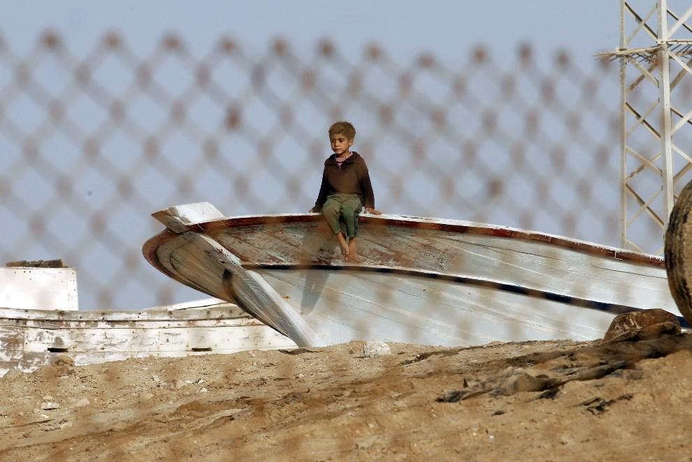 24.STREFA GAZAY, Rafah, 7 marca 2014: Palestyński chłopiec przygląda się demonstracji w Strefie Gazy. AFP PHOTO/ SAID KHATIB