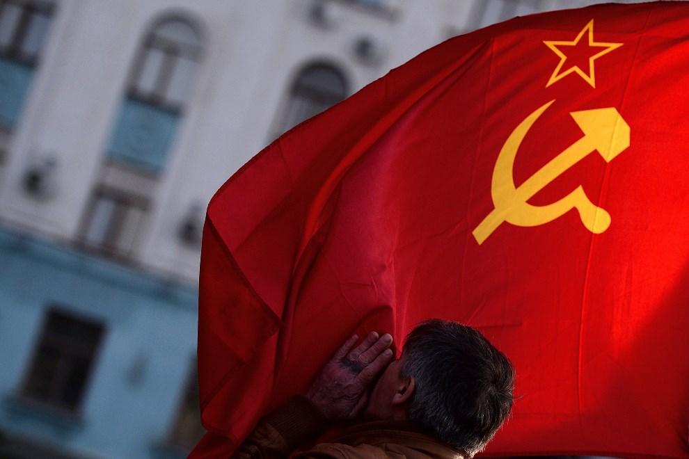 23.UKRAINA, Symferopol, 16 marca 2014: Mężczyzna całuje flagę Związku Radzieckiego. AFP PHOTO / FILIPPO MONTEFORTE