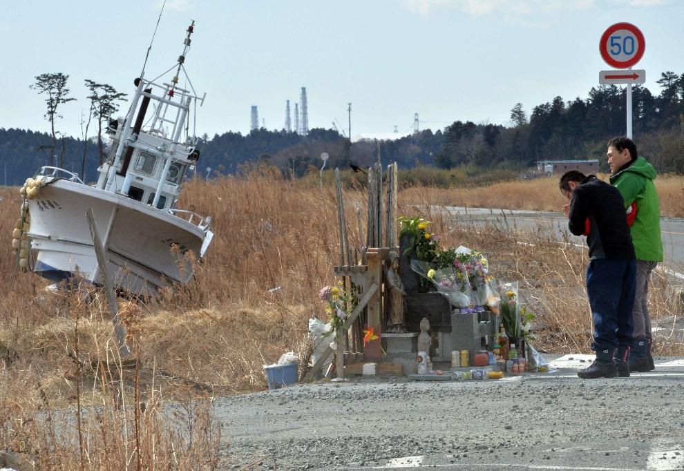 25.JAPONIA, Fukuszima, 11 marca 2014: Mężczyźni modlą się przed ołtarzem upamiętniającym ofiary tsunami. AFP PHOTO / YOSHIKAZU TSUNO