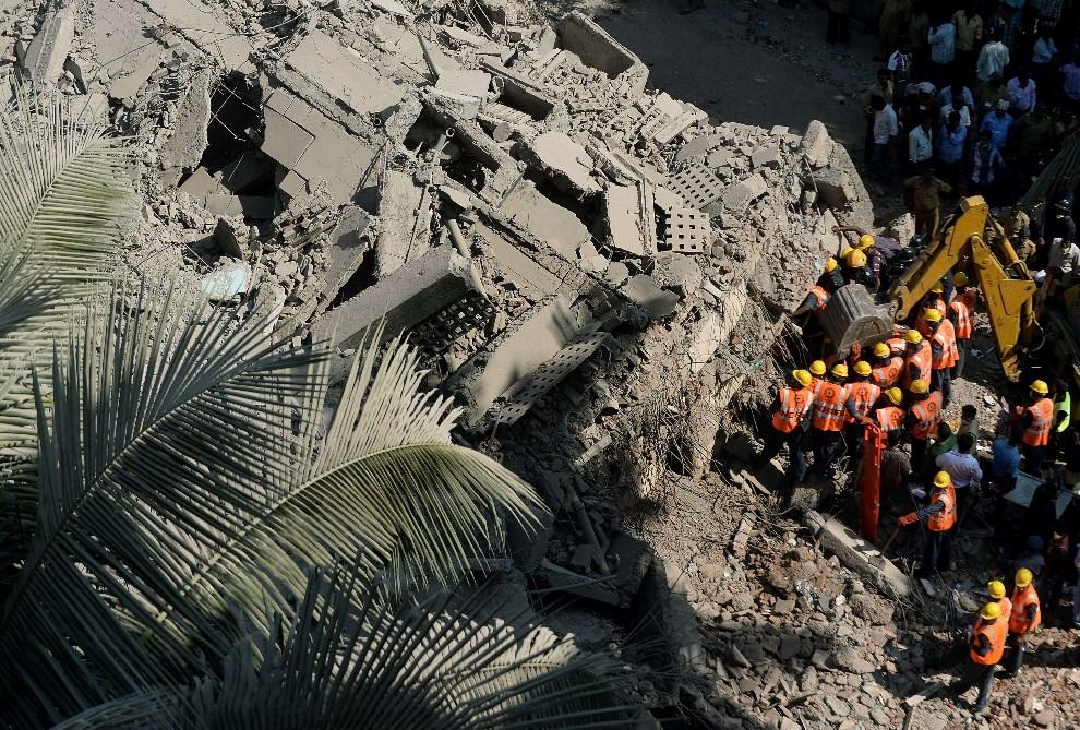 24.INDIE, Bombaj, 14 marca 2014: Ekipy ratownicze przeszukują gruzowisko zawalonego domu mieszkalnego. AFP PHOTO/ PUNIT PARANJPE