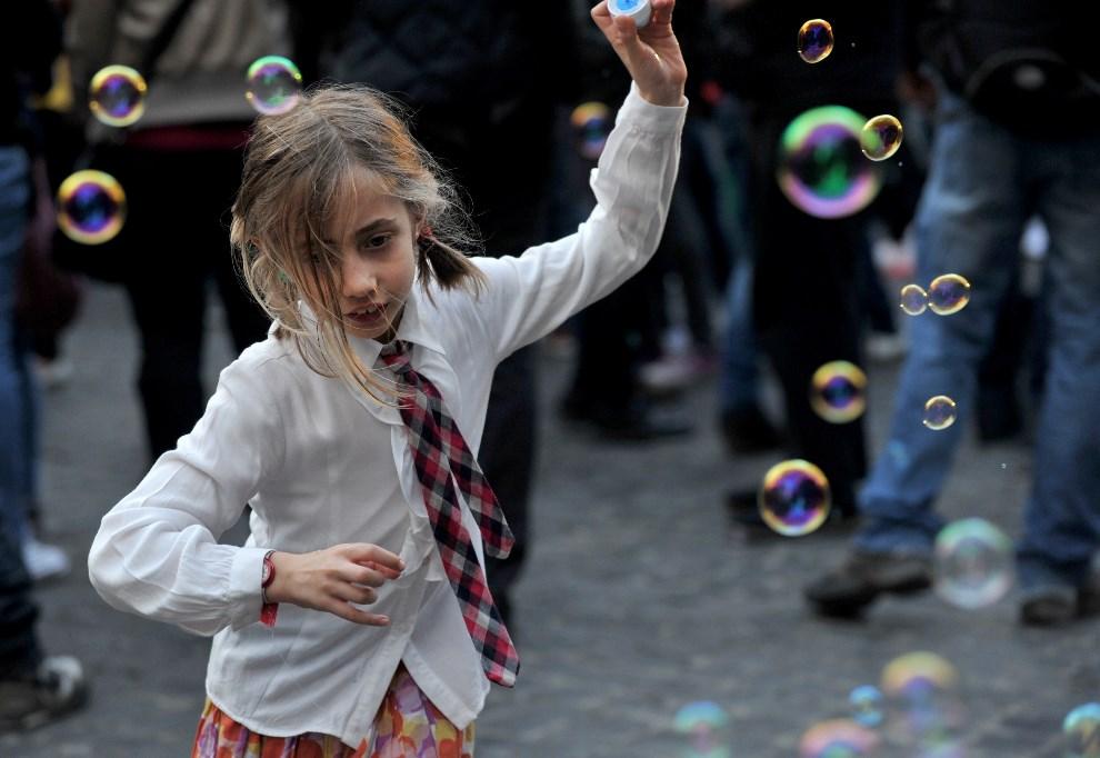 24.WŁOCHY, Rzym, 22 marca 2014: Dziewczyna bawiąca się bańkami mydlanymi. TOPSHOTS/AFP PHOTO/TIZIANA FABI
