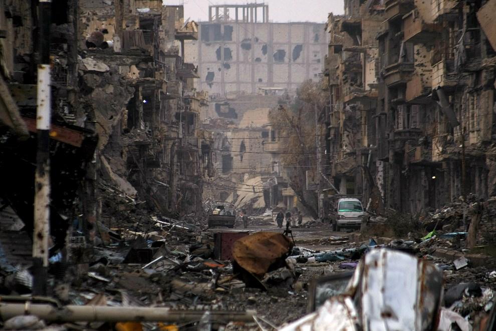 26.SYRIA, Deir Ezzor, 4 stycznia 2014: Zniszczona ulica prowadząca do północnej części Deir Ezzor. AFP PHOTO / AHMAD ABOUD