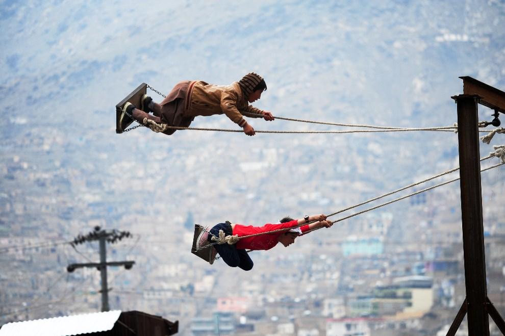 25.AFGANISTAN, Kabul, 21 marca 2014: Chłopcy na huśtawkach w pobliżu świątyni Sahki. AFP PHOTO/ROBERTO SCHMIDT