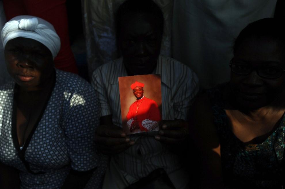 27.HAITI, Port-au-Prince, 9 marca 2014: Kobieta trzymająca zdjęcie pierwszego haitańskiego kardynała, Chibly Langloisa. AFP PHOTO/Hector RETAMAL