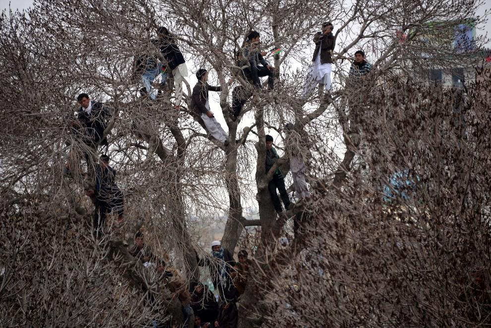 26.AFGANISTAN, Mazari-i-Sharif, 21 marca 2014: Mężczyźni przyglądają się świętującym Nowruz. AFP PHOTO/FARSHAD USYAN