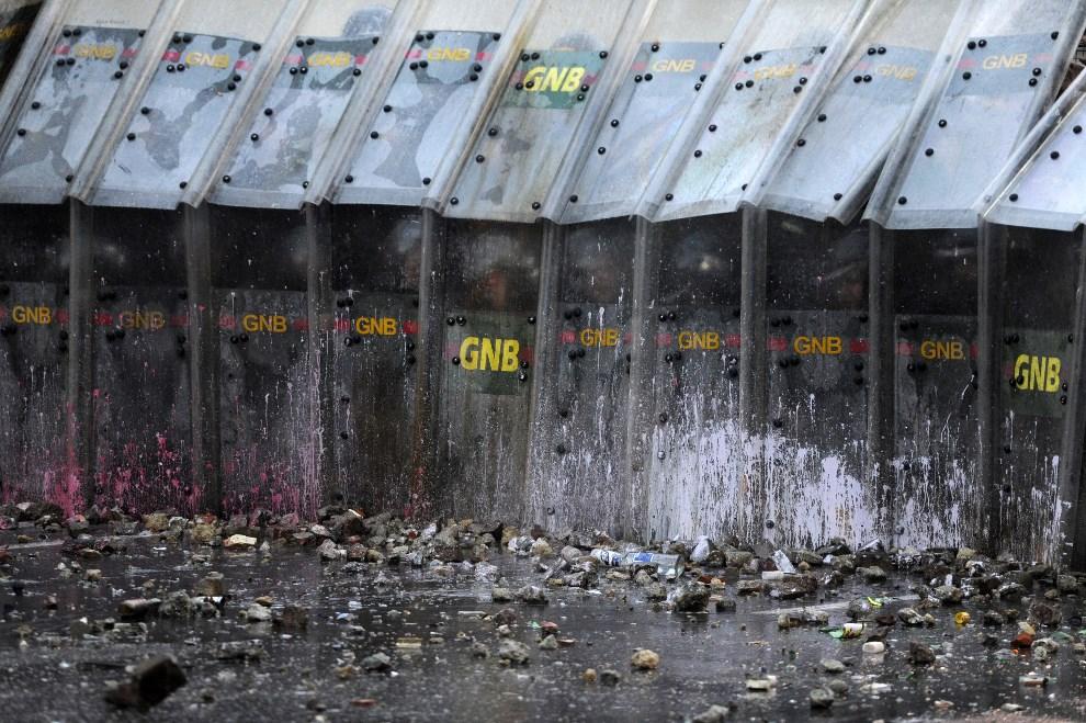 27.WENEZUELA, Caracas, 28 lutego 2014: Oddział policji chroniący się przed protestującymi opozycjonistami. AFP PHOTO/ LEO RAMIREZ