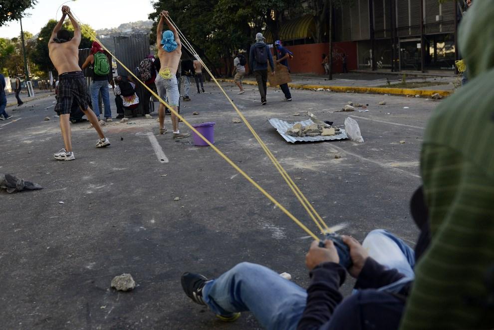 28.WENEZUELA, Caracas, 2 marca 2014: Opozycjoniści ostrzeliwują pozycje zajmowane przez policję. AFP PHOTO /LEO RAMIREZ