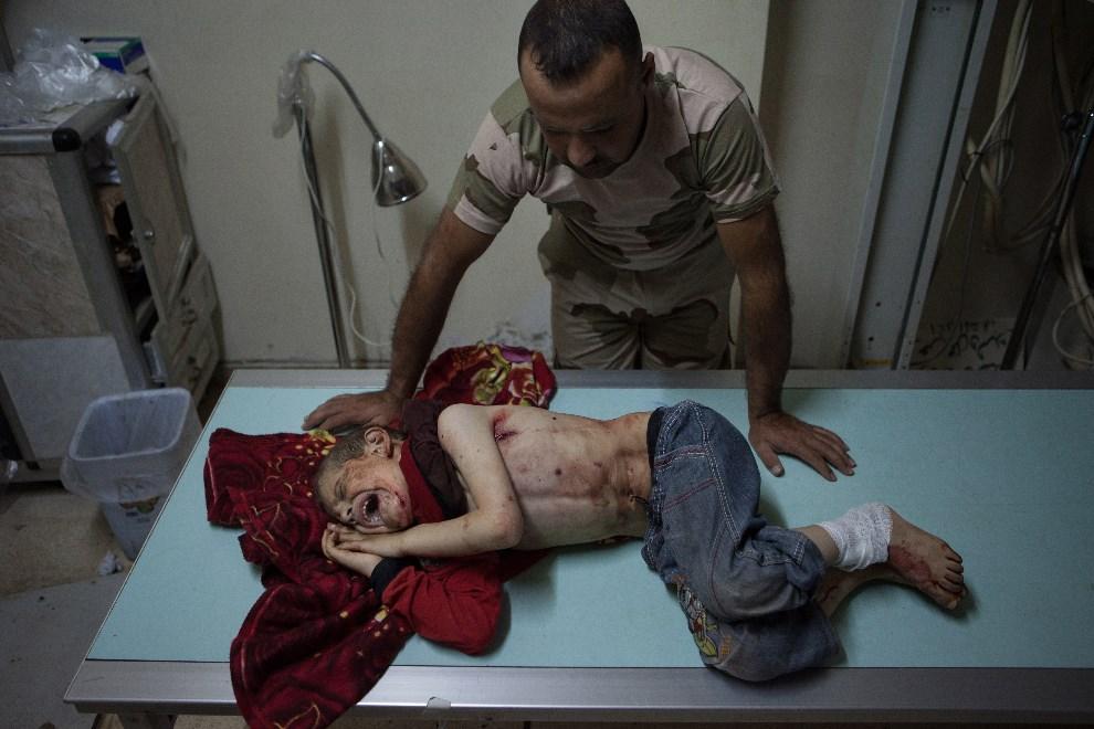 29.SYRIA, Al-Bara, 10 lipca 2013: Rebeliant stoi przy w szpitalu przy rannym siedmioletnim chłopcu. AFP PHOTO / DANIEL LEAL-OLIVAS