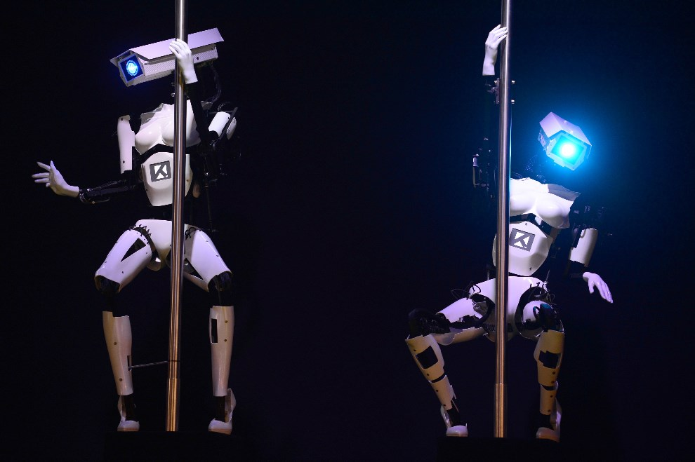 """29.NIEMCY, Hanower, 9 marca 2014: Roboty tańczące """"na rurach"""" podczas targów CeBIT. AFP PHOTO / JOHN MACDOUGALL"""