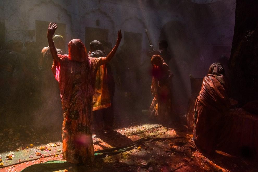 28.INDIE, Vrindavan, 14 marca 2014: Wdowy, pokryte kolorowymi proszkami, tańczą podczas święta Holi. AFP PHOTO/Rebecca Conway
