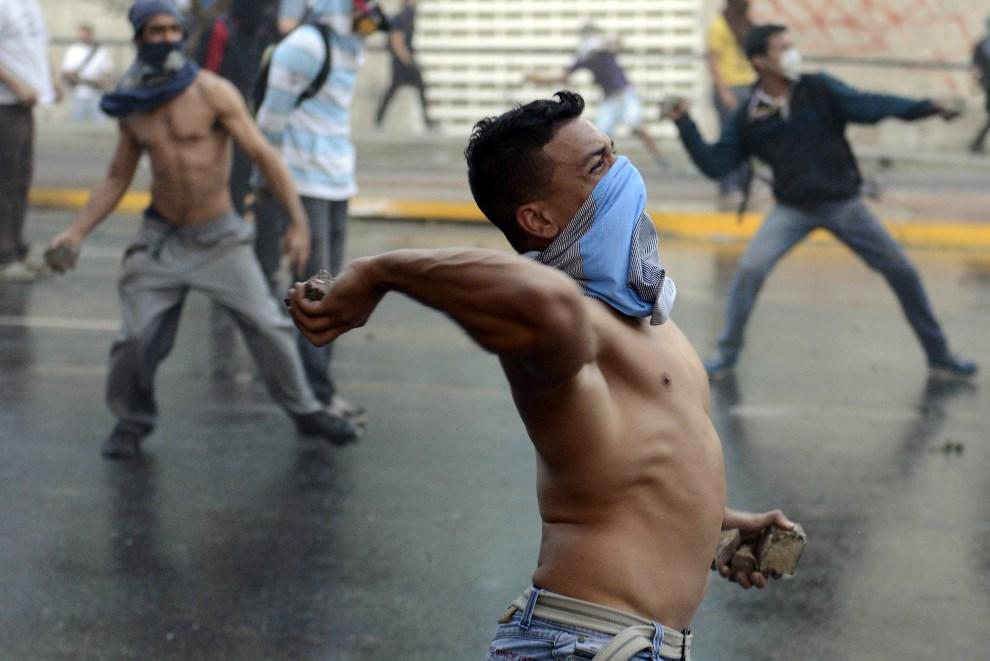 29.WENEZUELA, Caracas, 28 lutego 2014: Demonstrujący rzucają kamieniami w kierunku policjantów. AFP PHOTO/ LEO RAMIREZ
