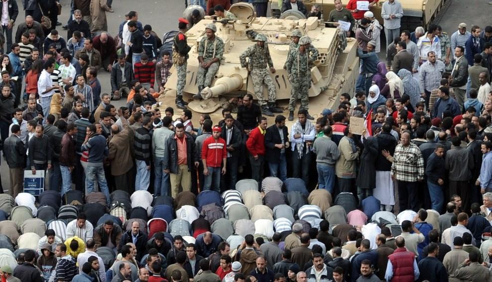 29.EGIPT, Kair, 30 stycznia 2011: Egipcjanie modlą się przy Abramsie podczas protestów na Placu Tahrir. AFP PHOTO/MIGUEL MEDINA