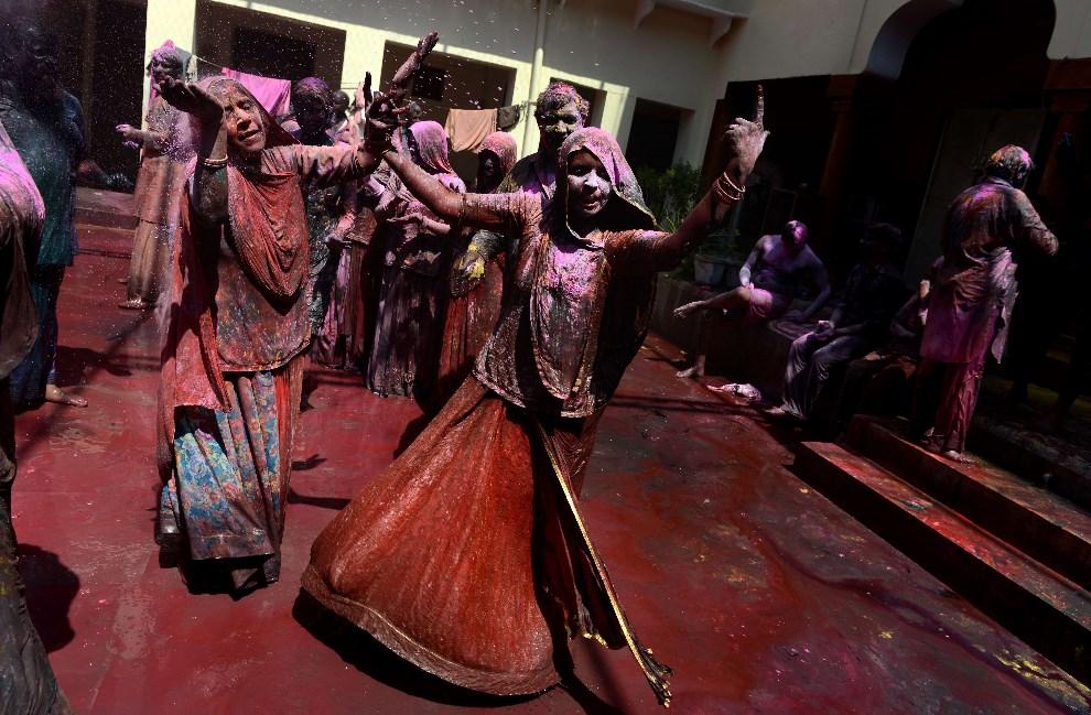 29.INDIE, Vrindavan, 17 marca 2014: Wierni, pokryci kolorowymi proszkami, bawią się podczas Holi. AFP PHOTO/Chandan KHANNA