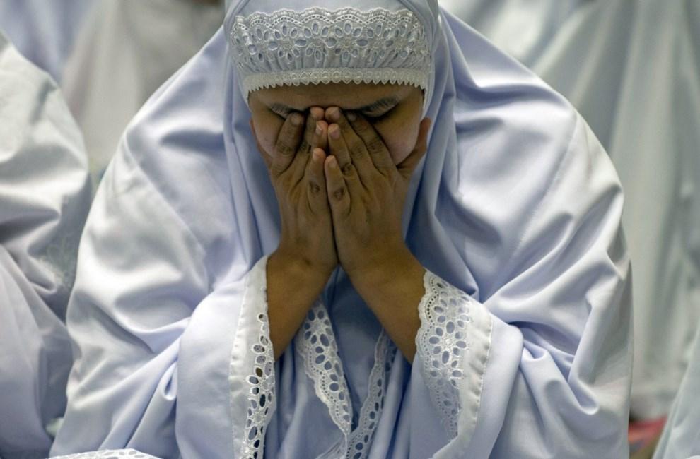 2.MALEZJA, Kuala Lumpur, 13 marca 2014: Muzułmanka modląca się za pasażerów zaginionego lotu MH370. AFP PHOTO / MOHD RASFAN
