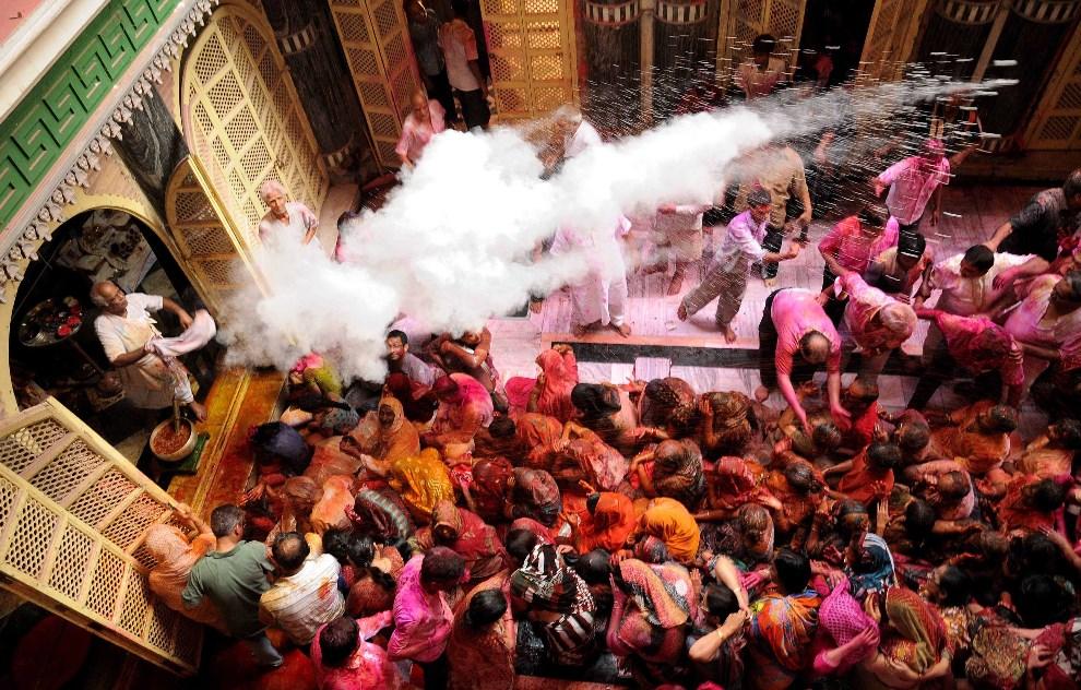 2.INDIE, Kolkata, 17 marca 2014: Kapłan rozrzuca kolorowe proszki na zebranych wiernych. AFP PHOTO/STR