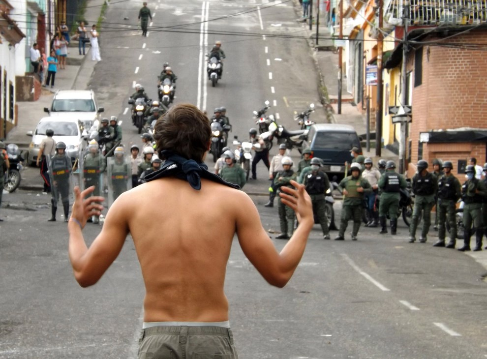 30.WENEZUELA, San Cristobal, 27 lutego 2014: Protestujący na tle Gwardii Narodowej. AFP PHOTO/ ORLANDO PARADA
