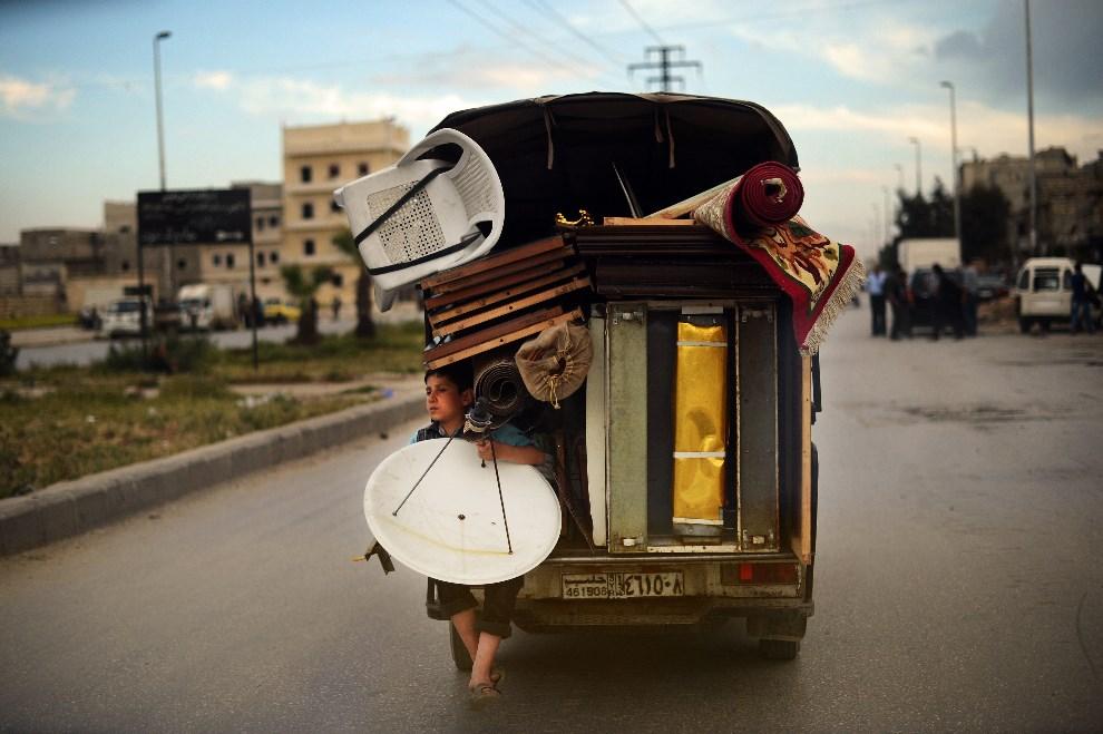 31.SYRIA, Aleppo, 15 kwietnia 2013: Chłopiec na ciężarówce przewożącej dobytek jego rodziny. AFP PHOTO / DIMITAR DILKOFF