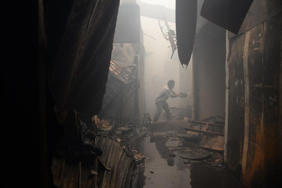 30.GWATEMALA, Gwatemala, 25 marca 2014: Mężczyzna dogasza ogień w swoim sklepie. AFP PHOTO/Johan ORDONEZ