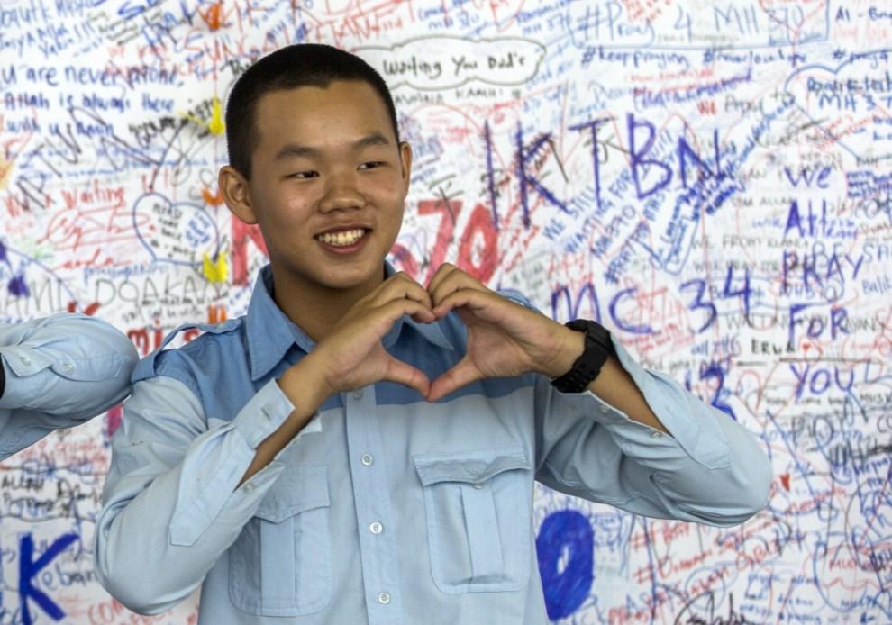 """30.MALEZJA, Kuala Lumpur, 19 marca 2014: Turysta fotografujący się przed """"ścianą nadziei"""" na lotnisku w Kuala Lumpur. EPA/AHMAD YUSNI Dostawca: PAP/EPA."""