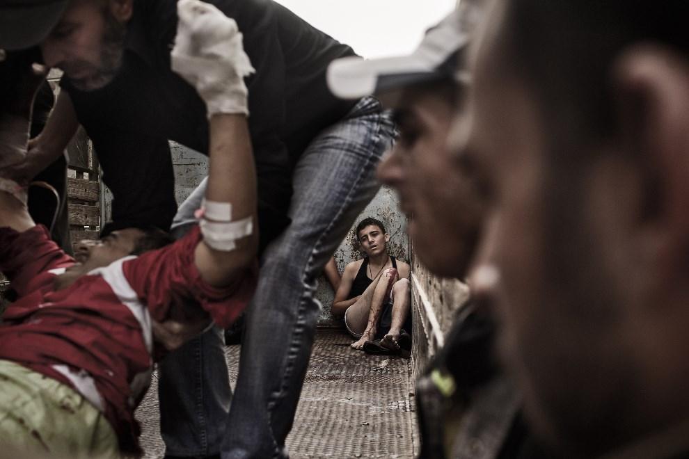 32.SYRIA, Aleppo, 21 października 2013: Chłopiec na pace ciężarówki przewożącej rannych. AFP PHOTO/FABIO BUCCIARELLI