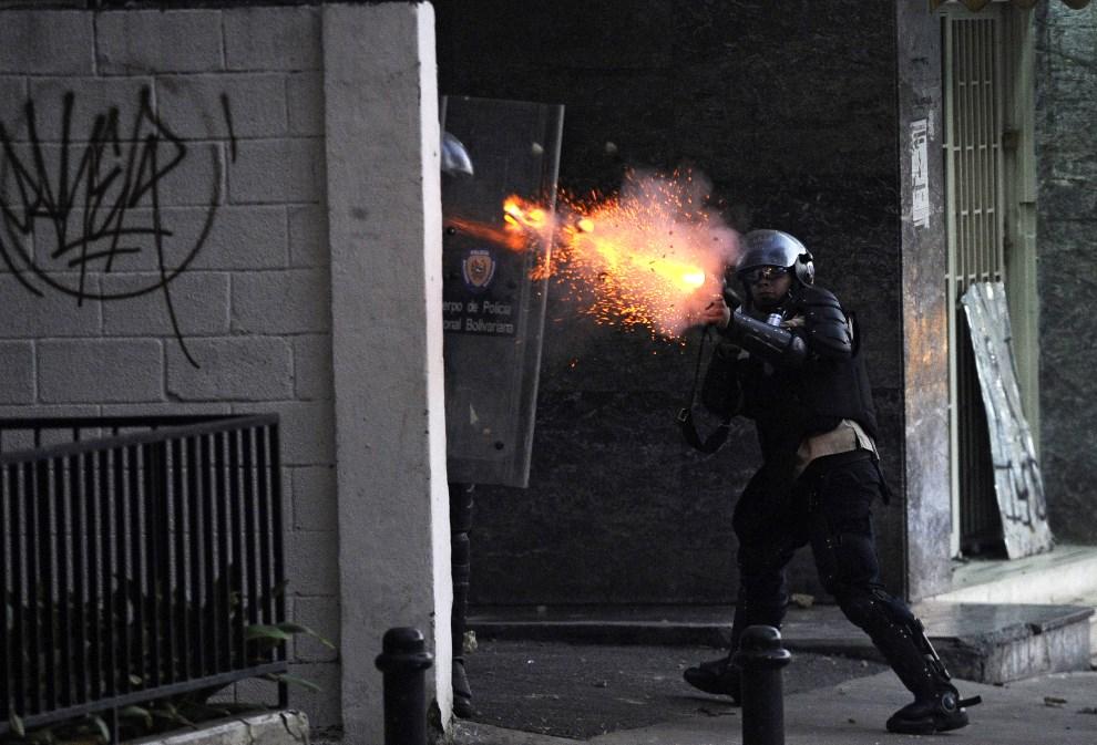 31.WENEZUELA, Caracas, 3 marca 2014: Gwardzista miotający pojemniki z gazem. AFP PHOTO /LEO RAMIREZ