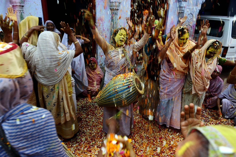 31.INDIE, Vrindavan, 17 marca 2014: Kobiety rzucające płatki kwiatów podczas zabawy. AFP PHOTO/Chandan KHANNA