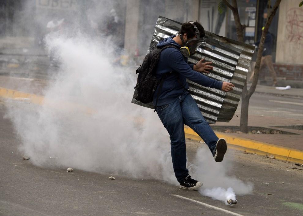 32.WENEZUELA, Caracas, 2 marca 2014: Opozycjonista kopie w pojemnik z gazem. AFP PHOTO / JUAN BARRETO