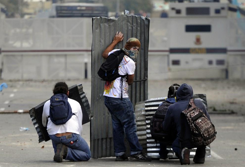 33.WENEZUELA, Caracas, 2 marca 2014: Opozycjoniści chronią się za arkuszami z blachy. AFP PHOTO /LEO RAMIREZ