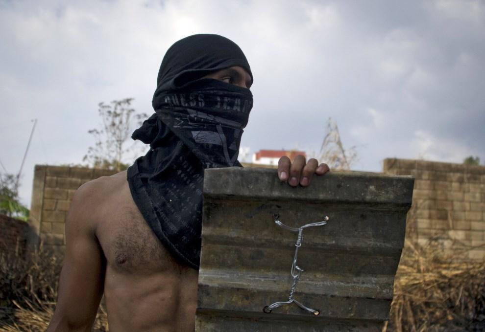 34.WENEZUELA, San Cristobal, 23 lutego 2014: Protestujący z prowizoryczną tarczą. AFP PHOTO / LUIS ROBAYO