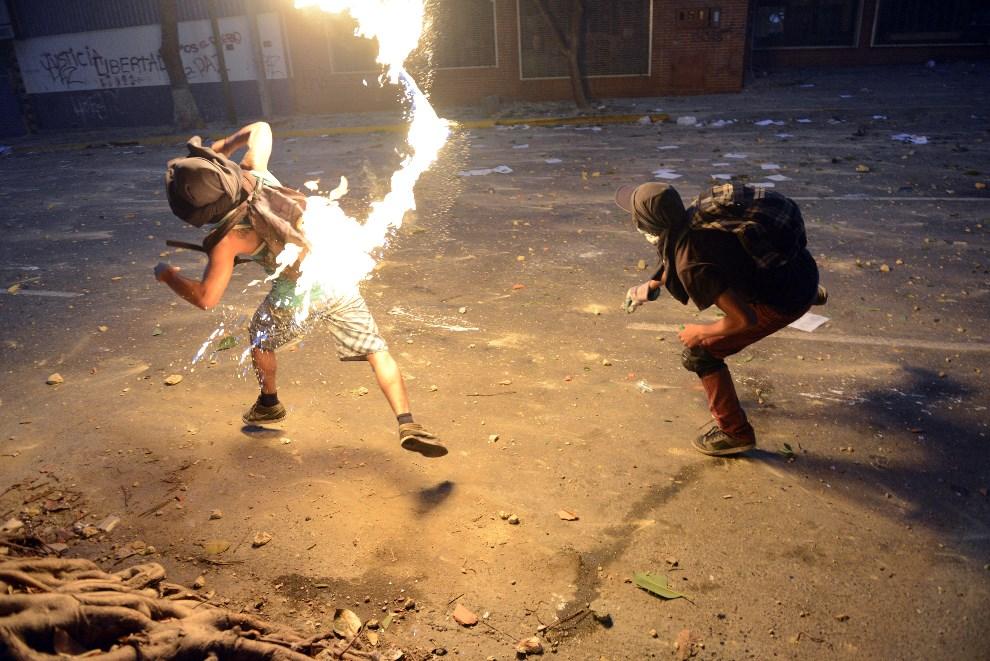 35.WENEZUELA, Caracas, 3 marca 2014: Opozycjoniści atakują policjantów koktajlami Mołotowa. AFP PHOTO /LEO RAMIREZ