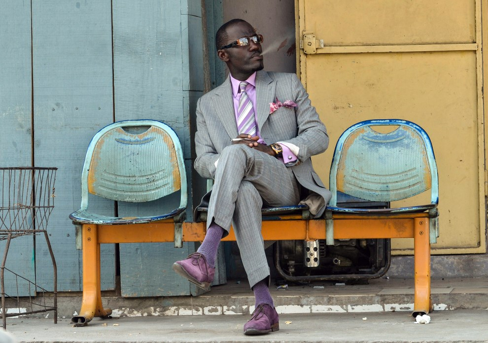 "35.KONGO, Brazzaville, 17 marca 2014: Sapeur Patience Moutala, członek grupy ""Red Devils"" reprezentującej ruch ""La Sape"" (akronim: ""Societe des Ambianceurs et des   Personnes Elegantes"" (Stowarzyszenie na rzecz popierania eleganckich ludzi). AFP PHOTO / JUNIOR D. KANNAH"