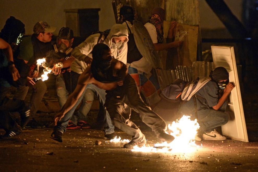 36.WENEZUELA, Caracas, 28 lutego 2014: Protestujący atakujący policjantów. AFP PHOTO/ JUAN BARRETO