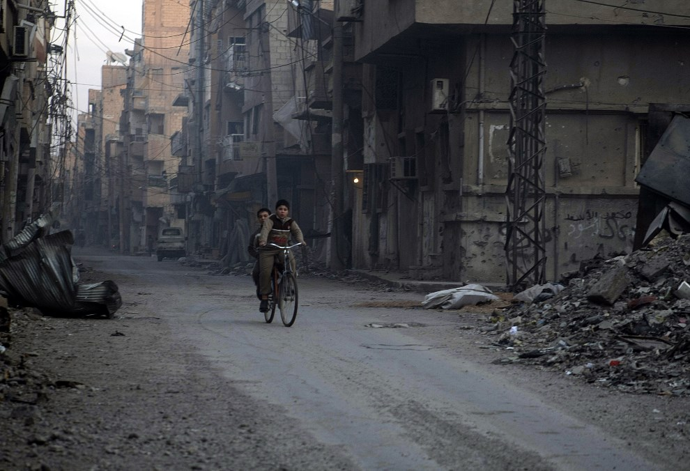 36.SYRIA, Deir Ezzor, 10 lutego 2014: Chłopcy na rowerze przejeżdżają między ruinami w mieścei Deir Ezzor. AFP PHOTO / AMHAD ABOUD