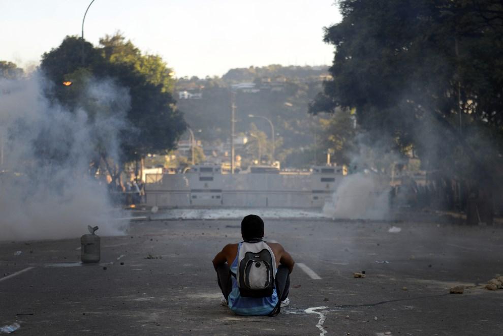 39.WENEZUELA, Caracas, 2 marca 2014: Opozycjonista siedzi przed barykadą wzniesioną przez policję. AFP PHOTO /LEO RAMIREZ