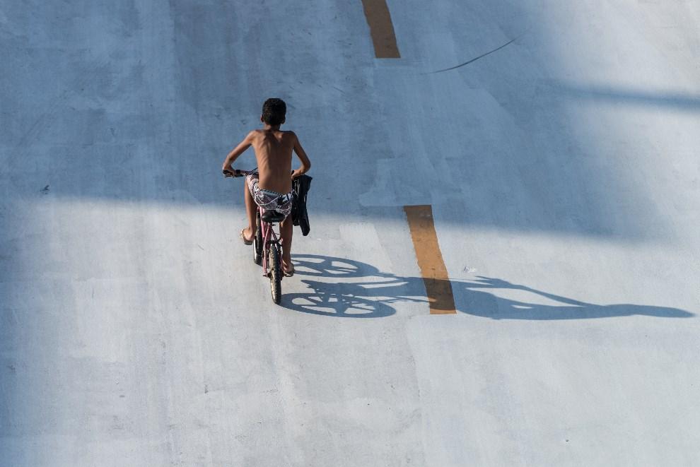 43.BRAZYLIA, Rio de Janeiro, 28 lutego 2014: Chlopak na rowerze przejeżdża przez Sambodrom. AFP PHOTO / YASUYOSHI CHIBA
