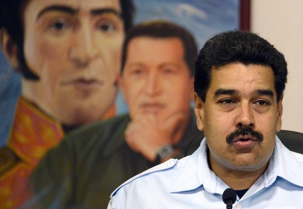 4.WENEZUELA, Caracas, 15 listopada 2013: Nicolas Maduro na tle portretów Hugo Chaveza i Simona Bolivara. AFP PHOTO/JUAN BARRETO