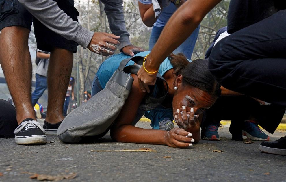 4.WENEZUELA, Caracas, 12 marca 2014: Kobieta ranna podczas antyrządowych zamieszek w Caracas. AFP PHOTO/LEO RAMIREZ