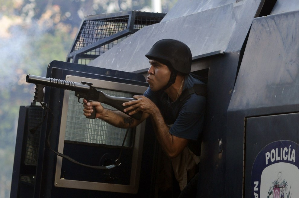 4.WENEZUELA, Caracas, 22 marca 2014: Policjant strzela pojemnikami z gazem podczas zamieszek w Caracas. AFP PHOTO/LEO RAMIREZ
