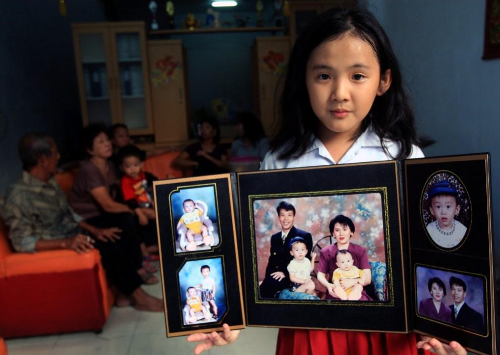 4.INDONEZJA, Medan, 25 marca 2014: Ayu Suliasti, której rodzice byli na pokładzie zaginionego samolotu, pokazuje rodzinne zdjęcia. EPA/DEDI SAHPUTRA Dostawca:   PAP/EPA.