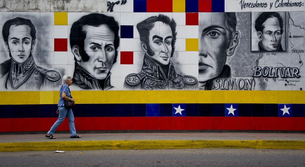 5.WENEZUELA, San Antonio, 25 lutego 2014: Kobieta mija mural z wizerunkiem Simona Bolivara. AFP PHOTO / LUIS ROBAYO