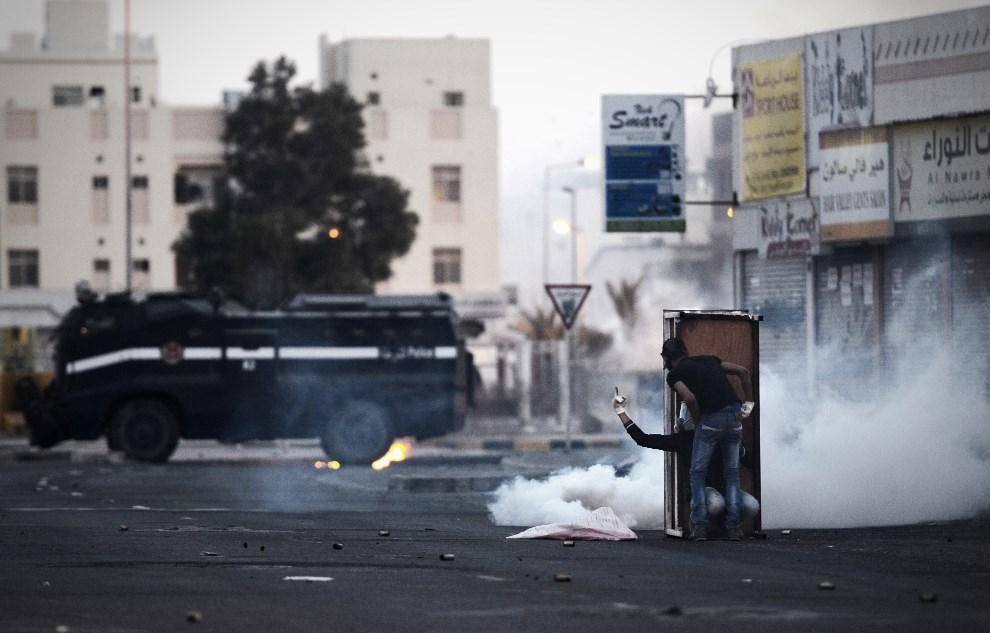 5.BAHRAJN, Sytra, 18 marca 2014: Protestujący mężczyźni chowają się przed policją za prowizoryczną tarczą. AFP PHOTO/MOHAMMED AL-SHAIKH