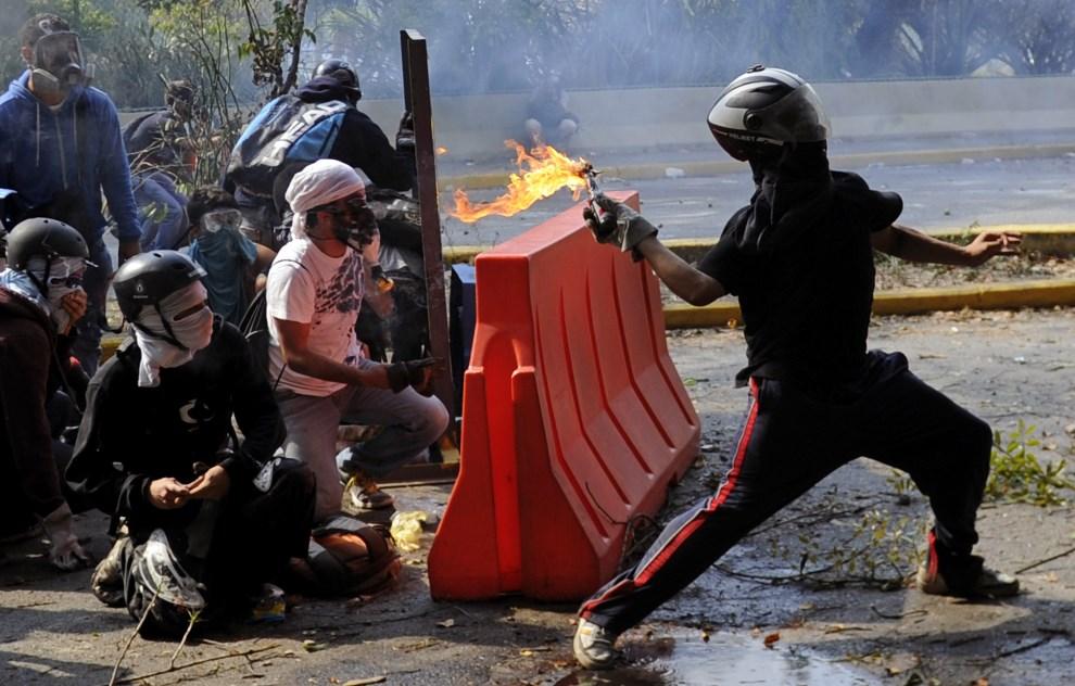 5.WENEZUELA, Caracas, 12 marca 2014: Student rzucający koktajlem Mołotowa w kierunku oddziałów policji. AFP PHOTO/LEO RAMIREZ
